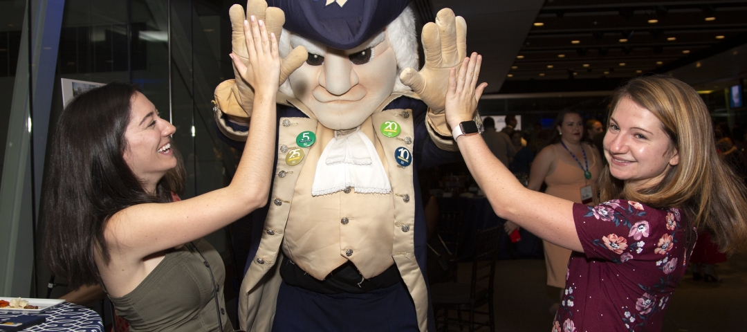 Two women high five the GW university George Washington mascot at a party.