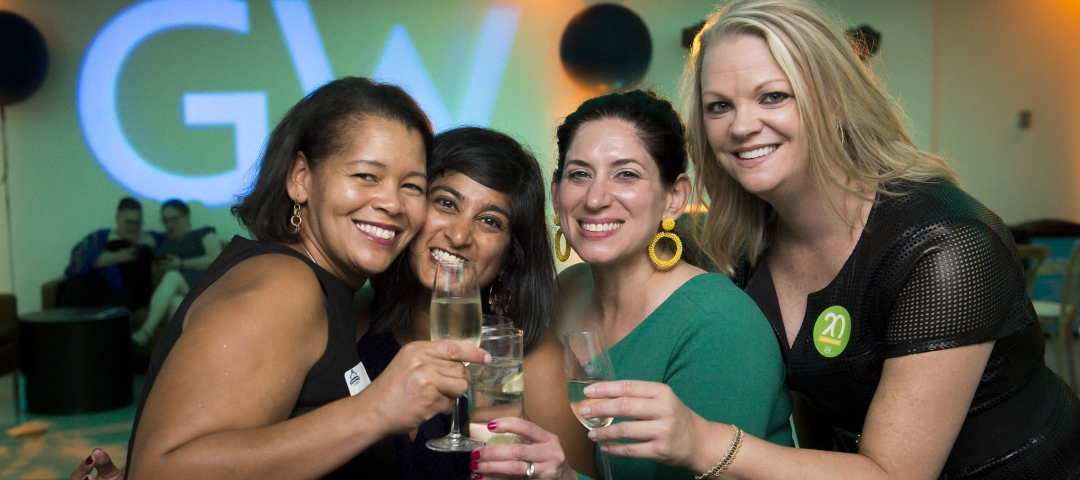 Group of four women hold champagne classes during a college reunion party.