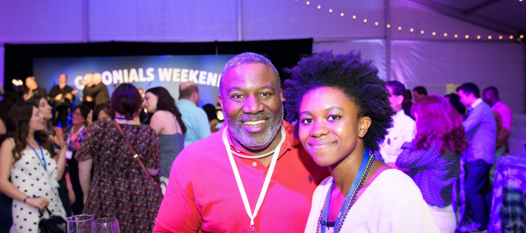 A father and daughter pose for a photo under a party tent.