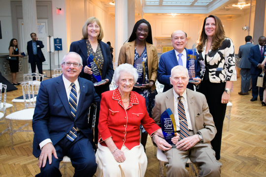 Group of awardees gather at ceremony for photo with university leaders.